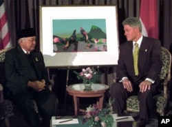 FILE - President Bill Clinton and Indonesian President Suharto meet at the 1997 APEC Summit in Vancouver, British Columbia, Nov. 24, 1997.