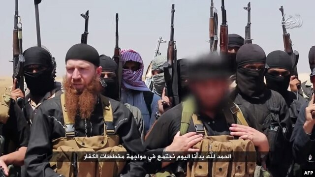FILE - An image made available by the Jihadist media outlet al-Itisam Media on June 29, 2014, allegedly shows members of the Islamic State, including military leader and Georgia native, Abu Omar al-Shishani (Tarkhan Batirashvili) (C-L) and ISIL sheikh Abu Mohammed al-Adnani (C-R), whose picture was blurred from the source to protect his identity, speaking at an unknown location between the Iraqi Nineveh province and the Syrian town of Al-Hasakah.