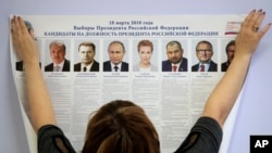 A polling station employee hangs a list of candidates for the 2018 Russian presidential election during preparations for the election at a polling station in St.Petersburg, Russia, March 16, 2018. The presidential elections will be in Russia March 18, 2018.