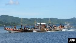 FILE - Philippine fishermen aboard their motorized boat sail along Ulugan Bay, in Puerto Princesa, Palawan island, south of Manila before heading to the open sea facing south China sea to fish.