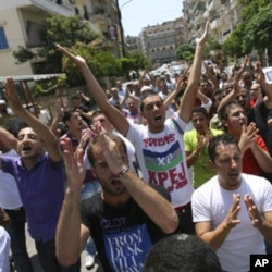 Protesters shout slogans as they gesture during a protest organised by Lebanese and Syrians living in Lebanon, to express solidarity with Syria's anti-government protesters, as they march in Tripoli, northern Lebanon, July 15, 2011. REUTERS/Omar Ibrahim (