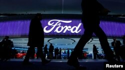 FILE - Attendees walk by the Ford display at the North American International Auto Show in Detroit, Jan. 11, 2016.