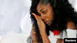 Myeshia Johnson, widow of U.S. Army Sergeant La David Johnson, who was among four special forces soldiers killed in Niger, sits with her daughter, Ah'Leeysa Johnson at a graveside service in Hollywood, Florida, Oct. 21, 2017.