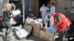 FILE - Volunteers and doctors unload a car with medical supplies from a volunteer organization to the army, at a hospital in Artemovsk, Donetsk region, Ukraine, Sept. 18, 2014.