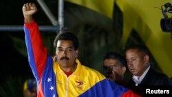 Kandidat presiden Venezuela, Nicolas Maduro, mengepalkan tangannya menyusul pengumuman kemenangannya dalam pemilihan presiden khusus untuk menggantikan mendiang Hugo Chavez. (Reuters/Tomas Bravo)