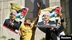 Người dân Palestine giơ cao những tấm áp phích có hình Tổng thống Mahmoud Abbas để ủng hộ những nỗ lực của ông trong việc bảo đảm một sự nâng cấp ngoại giao tại LHQ, 29/11/2012.