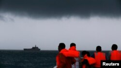 Rescue team members look out toward the ship KRI Banda Aceh as dark clouds fill the sky during a search operation for passengers onboard AirAsia Flight 8501 in the Java Sea, Jan. 4, 2015.