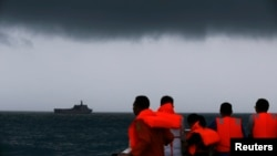 Anggota Tim SAR melihat ke arah kapal KRI Banda Aceh semantara awan gelap menggantung di langit selama operasi pencarian korban kecelakaan pesawat AirAsia 8501 di Laut Jawa (4/1).