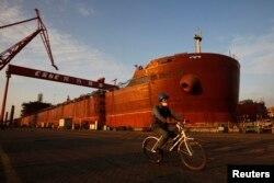 지난 2011년 중국 남부 광저우시 룽쉐 조선소에서 한 노동자가 '중국선박중공집단공사(중선중공)'가 제조한 선박 옆으로 자전거를 타고 지나가고 있다.