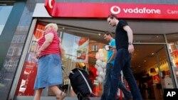2014年6月6日星期五大眾走過倫敦沃達豐商店。(資料圖片)