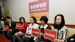 In this photo taken March 24, 2017, Lee Ching-yu, third from right holds up a photo of her missing husband and Taiwanese pro-democracy activist Lee Ming-che during a press conference with other representatives of non-governmental organizations calling for help to find his whereabouts in Taipei, Taiwan.