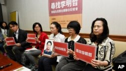 FILE - In this photo taken Friday, March 24, 2017, Lee Ching-yu, third from right holds up a photo of her missing husband and Taiwanese pro-democracy activist Lee Ming-che during a press conference.