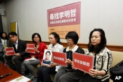 In this photo taken Friday, March 24, 2017, Lee Ching-yu, third from right holds up a photo of her missing husband and Taiwanese pro-democracy activist Lee Ming-che during a press conference with other representatives of non-governmental organizations cal