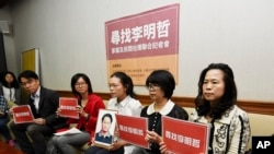 FILE - In this photo taken March 24, 2017, Lee Ching-yu holds a photo of her missing husband and Taiwanese pro-democracy activist Lee Ming-che during a press conference in Taipei, Taiwan.