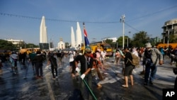 Anti-government protesters sweep streets in front of the Democracy Monument in Bangkok, Thailand, Wednesday, Dec. 4, 2013.