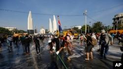 Para demonstran anti-pemerintah menyapu jalan di depan Monumen Demokrasi di Bangkok, Thailand (4/12). (AP/Vincent Thian)