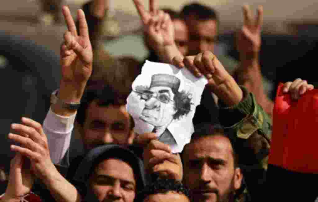 """Libyan protesters flash the V for """"victory"""" sign and hold a caricature of leader Moamer Kadhafi during a rally in the eastern city of Tobruk on February 24, 2011 as residents of Libya's dissident-held east, frenzied by a deadly crackdown by Kadhafi's crum"""
