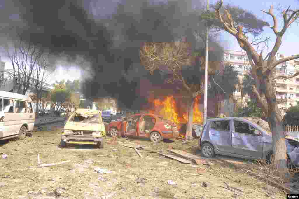 "Vehicles burn after an explosion in central Damascus February 21, 2013. Syrian state media blamed what it said was a suicide bombing on ""terrorists"" battling President Bashar al-Assad."