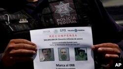 """ໃນພາບນີ້ ຖ່າຍເມື່ອ ວັນທີ 16 ກໍລະກົດ 2015, ຕຳຫລວດລັດຖະບານກາງ ເມັກຊິກໂກ ສະແດງໃຫ້ເຫັນ ໃບປະກາດ ໃຫ້ລາງວັນ ສຳຫລັບຂໍ້ມູນທີ່ນຳໄປສູ່ການຈັບກຸມ ລາຊາຄ້າຢາເສບຕິດ Joaquin """"El Chapo"""" Guzman ຜູ້ທີ່ໄດ້ແຫກຄຸກ ຫຼົບໜີ ຜ່ານອຸບໂມງ ໃຕ້ຄຸກ ລະຍະ 1.5 ກິໂລແມັດ ເມື່ອເດືອນ ກໍລະກົດປີກາຍນີ້ ໃນເມືອງ Almoloya ຢູ່ທາງກ້ຳຕາເວັນຕົກ ຂອງນະຄອນຫຼວງ Mexico City."""
