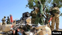 South Sudan army soldiers stand next to a destroyed motorcycle near Bor Airport in Jonglei state, Dec. 25, 2013.