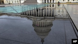 The U.S. Capitol is seen reflected after rain in Washington, Dec. 21, 2018.