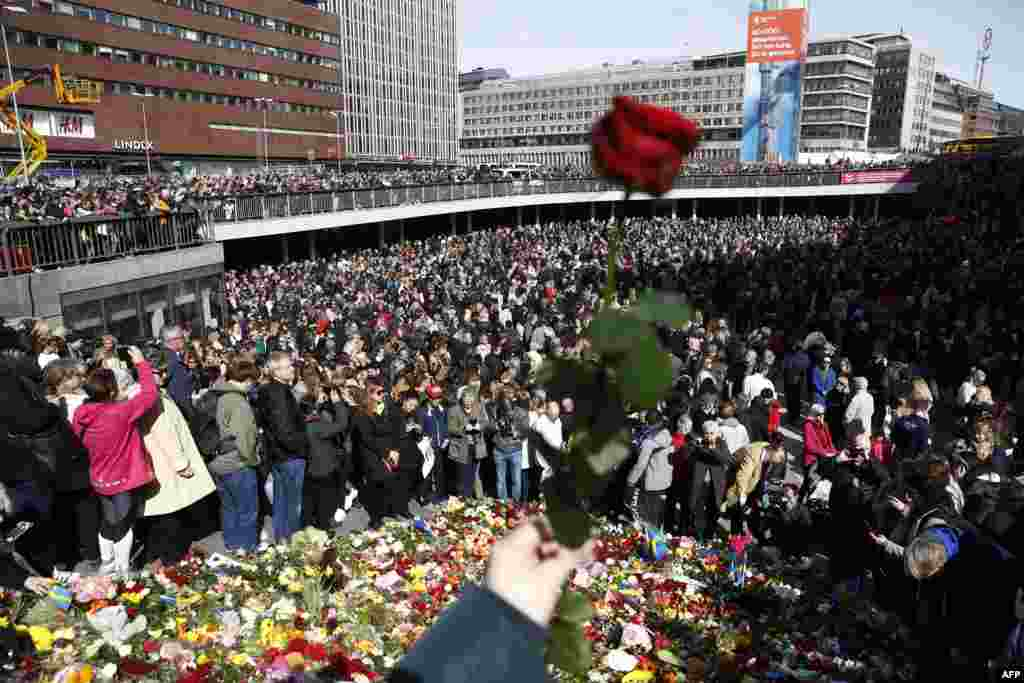 People attend a memorial ceremony at Sergels Torg plaza in Stockholm, near a department store  where a truck drove into two days before. Four people died and fifteen were injured.