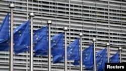 FILE - European Union flags flutter outside EU Commission headquarters in Brussels, Belgium, Oct. 28, 2015.