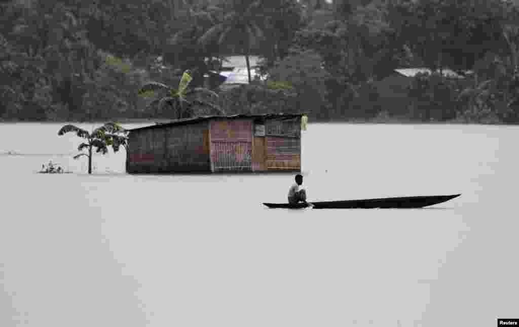 A villager uses a boat to cross flooded areas of Morigaon district in the northeastern Indian state of Assam.