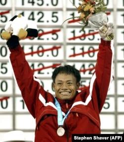 Atlet angkat besi nasional Erwin Abdullah merayakan setelah menerima medali perak dalam upacara penghargaan angkat besi 69 kg, 3 Oktober 2002 di Asian Games ke-14 di Busan. (Foto: AFP/Stephen Shaver)