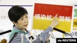 Tokyo Governor Yuriko Koike shows a banner reading 'Infection spread alert' during a news conference on the latest situation of the coronavirus disease (COVID-19) outbreak, in Tokyo, Japan, July 15, 2020, in this photo taken by Kyodo.