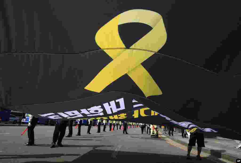 Workers carry a flag depicting a yellow ribbon as a sign of hope for the safe return of missing passengers of the sunken ferry Sewol during a May Day rally to pay tribute to the victims of the accident in Seoul, South Korea, Thursday, May 1, 2014.