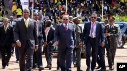President Omar al-Bashir of Sudan, center, arrives for the inauguration ceremony of Uganda's long-time president Yoweri Museveni in the capital Kampala, May 12, 2016.