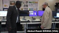 Des membres de la réunions regardent le matériel utilisé pour mener les recherches (Abdoul-Razak Idrissa / VOA).