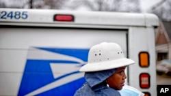 Jamesa Euler, agent de la poste américaine depuis 12 ans, distribue le courrier sous la pluie dans le quartier de Cabbagetown, 7 février 2013, à Atlanta. (AP Photo / David Goldman)