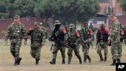 Tentara Kolombia (kanan dan kiri) mengawal para pemberontak dari Laskar Pembebasan Nasional (ELN) saat menyerahkan diri di basis militer di Cali, Kolombia, 16 Juli 2013 (Foto: dok).