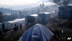 Des migrants se tiennent devant leurs tentes de fortune à l'extérieur du périmètre du camp de réfugiés surpeuplé de Moria sur l'île de Lesbos, en Grèce, le 28 janvier 2020.