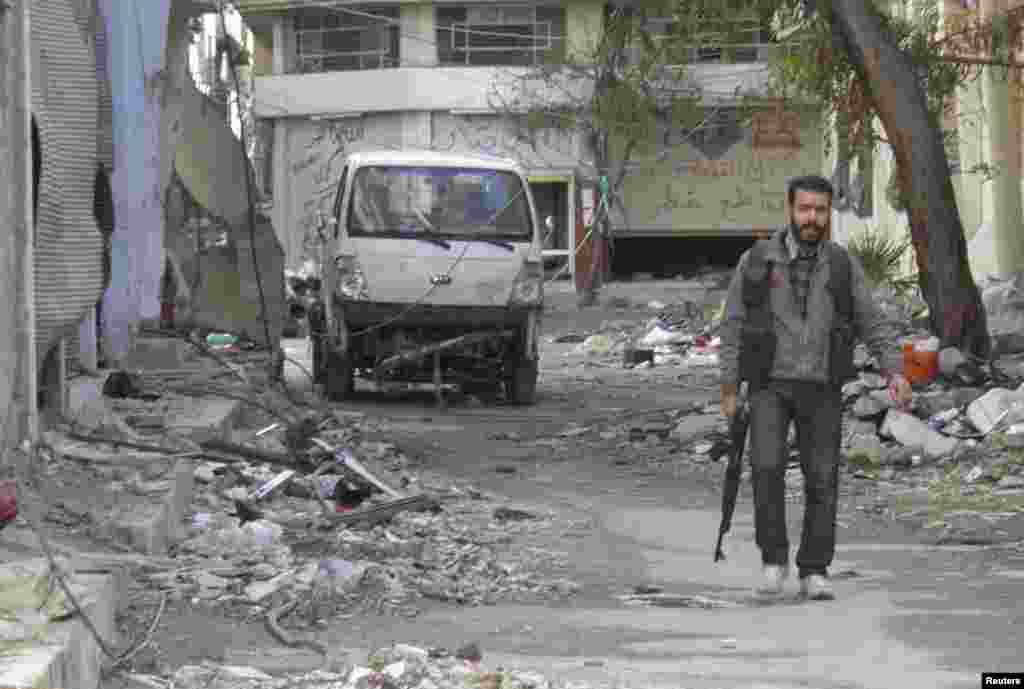 A Free Syrian Army fighter holds his weapon as he walks along a damaged street in the besieged area of Homs, Jan. 30, 2014.