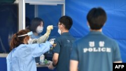 Medical workers in a booth take test samples for the COVID-19 coronavirus from South Korean police officers at Seoul Metropolitan Police Agency's maneuver headquarters in Seoul on August 19, 2020. - All police officers who were on duty during a rally on t