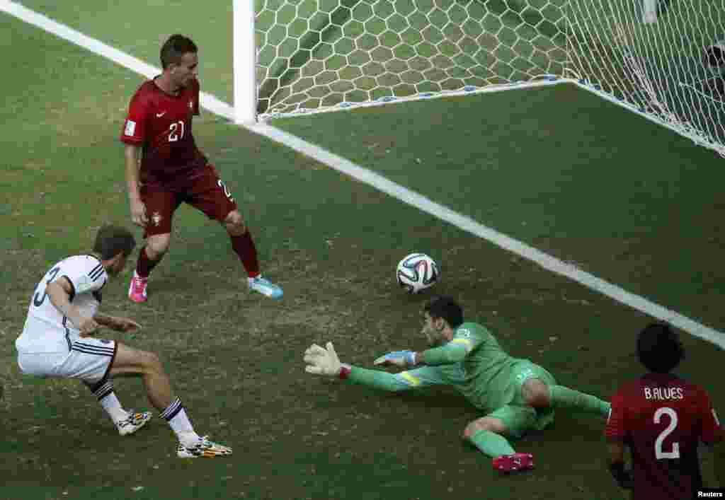 Germany's Thomas Mueller (L) shoots to score against Portugal for his hat-trick during their 2014 World Cup Group G soccer match at the Fonte Nova arena in Salvador, June 16, 2014.