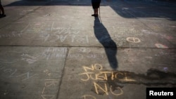 Messages written in a parking lot protest the police shooting of Michael Brown in Ferguson, Missouri, on Aug. 15, 2014.