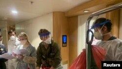 Personel medis Guardian Angels bersama para petugas dari Pusat Pengendalian dan Pencegahan Penyakit AS (CDC) bersiap memeriksa para tamu di kapal pesiar Grand Princess, di lepas pantai California, 5 Maret 2020. (Foto: Garda Nasional California via Reuters