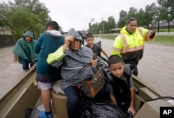 Evacuees ride in a boat down Tidwell Road as floodwaters from Tropical Storm Harvey rise in Houston, Aug. 28, 2017.