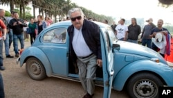 FILE - Uruguay's former President Jose Mujica arrives to cast his vote in Montevideo, Uruguay, Oct. 26, 2014.
