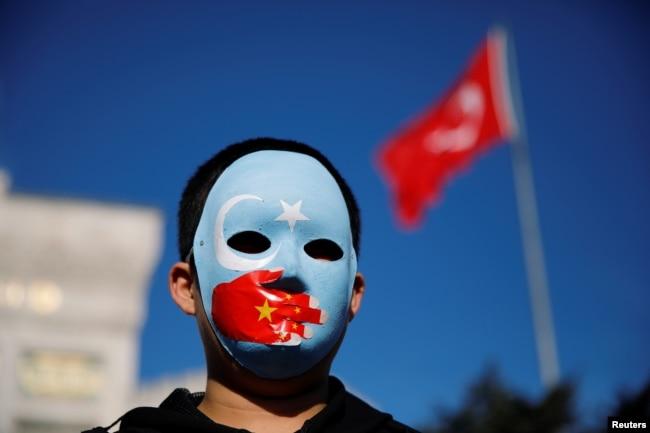 Seorang bocah etnis Uighur mengenakan topeng saat protes terhadap China di Istanbul, Turki, 14 Desember 2019. (Foto: Reuters)