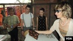 Pemilik salah satu industri batik Solo, Saud (kiri) mendampingi rombongan desainer Koefia Italia Giussepe (baju putih),Giorgia Donia (baju hitam), dan Bianca (paling kiri pegang cap/ stempel batik) saat berkunjung di kampung batik Laweyan Solo, Kamis sia