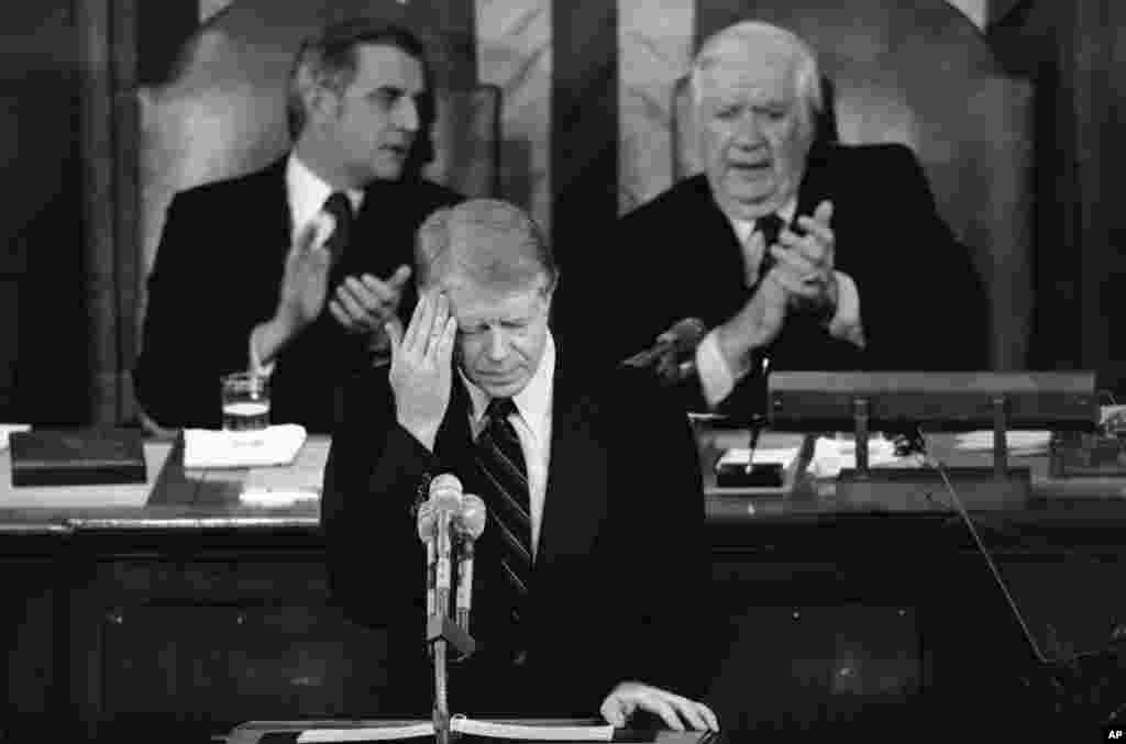 President Jimmy Carter touches his brow as he addresses those in the House chamber of the Capitol in Washington on Jan. 23, 1979.