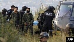 Vojnici čuvaju stražu dok meksička federalna policija nosi telo jedne od žrtava nesreće helikoptera u kojoj je poginuo i ministar unutrašnjih poslova Fransisco Blejk Mora