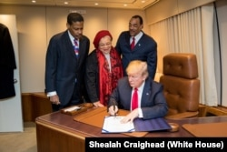 President Donald J. Trump, with Alveda King, center, niece of slain Civil Rights leader Dr. Martin Luther King Jr., and joined by Isaac Newton Farris Jr., left, nephew of Dr. King, and Bruce Levell of the National Diversity Coalition for Trump, right, signs the Martin Luther King Jr. National Historical Park Act, Jan. 8, 2018, aboard Air Force One, in Atlanta, Ga.