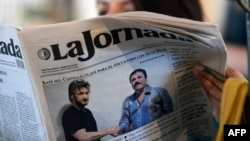 """A woman reads La Jornada newspaper in Mexico City, on January 10, 2016 which shows a picture of drug lord Joaquin Guzman, aka """"El Chapo"""" (R), shaking hands with US actor Sean Penn."""