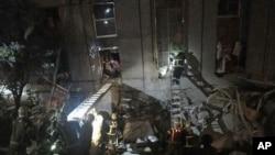 Rescatistas tratan de ingresar a un edificio de oficinas que cayó de lado en Tainán. Los socorristas trantan de salvar a decenas de personas atrapadas.